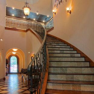 Cette photo montre un grand escalier courbe méditerranéen avec des marches en bois, des contremarches en ardoise et un garde-corps en métal.