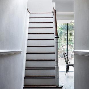 ロンドンの中くらいの木のヴィクトリアン調のおしゃれな折り返し階段 (フローリングの蹴込み板) の写真