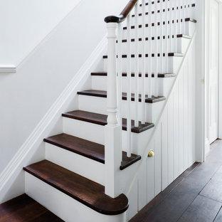 ロンドンの中サイズの木のヴィクトリアン調のおしゃれな折り返し階段 (フローリングの蹴込み板) の写真