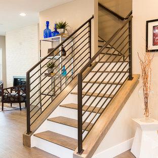 Imagen de escalera recta, urbana, de tamaño medio, con escalones de madera, contrahuellas de madera pintada y barandilla de metal