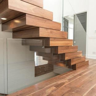 Foto di una grande scala sospesa minimalista con pedata in legno e alzata in legno