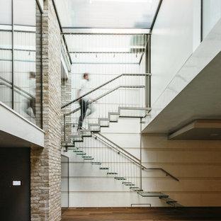 Diseño de escalera suspendida, contemporánea, grande, con contrahuellas de vidrio y escalones de vidrio