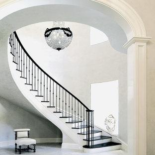 Ejemplo de escalera curva, tradicional, grande, con contrahuellas de madera pintada, barandilla de metal y escalones de madera