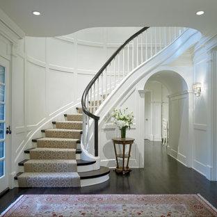Ejemplo de escalera curva, tradicional, de tamaño medio, con barandilla de madera, escalones de madera y contrahuellas de madera pintada