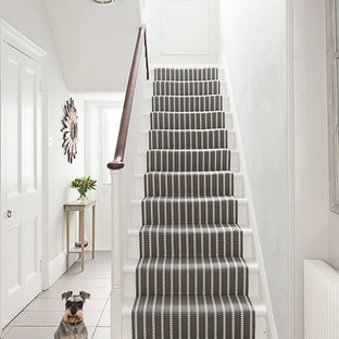 Traditional painted wood u-shaped staircase in Kent with painted wood risers.