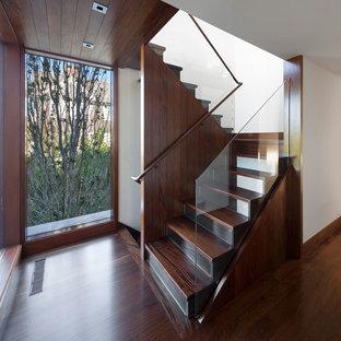 ニューヨークの木のコンテンポラリースタイルのおしゃれな折り返し階段 (ガラスの蹴込み板) の写真