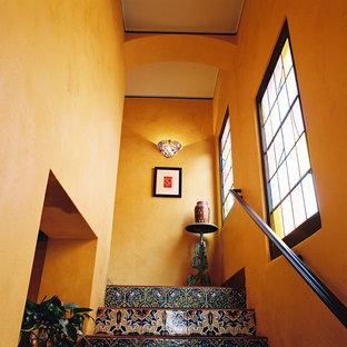 Diseño de escalera en L, mediterránea, grande, con contrahuellas con baldosas y/o azulejos, escalones con baldosas y barandilla de metal