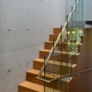 Photo of a medium sized and mixed modern wood u-shaped staircase in London with wood risers.