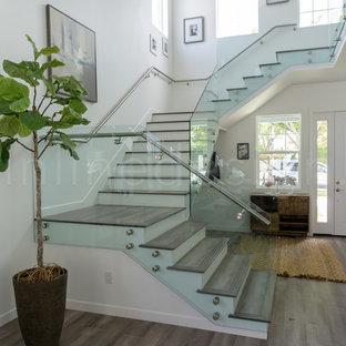 シアトルの中くらいの木のモダンスタイルのおしゃれな階段 (ガラスの蹴込み板、ガラスの手すり) の写真