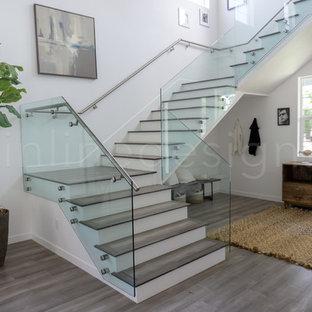 シアトルの中サイズの木のモダンスタイルのおしゃれな階段 (ガラスの蹴込み板、ガラスの手すり) の写真