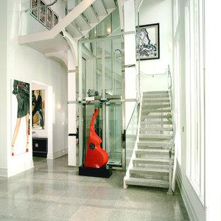 """Immagine di una scala a """"U"""" moderna di medie dimensioni con pedata in marmo, nessuna alzata e parapetto in vetro"""