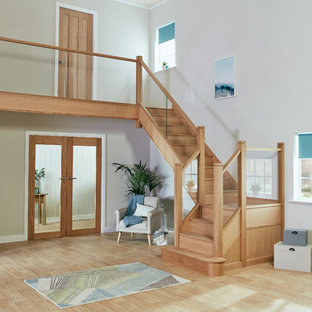 This is an example of a medium sized classic wood u-shaped glass railing staircase in Manchester with wood risers.