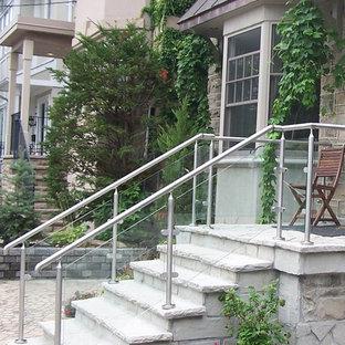 トロントの中サイズのタイルのコンテンポラリースタイルのおしゃれな直階段 (タイルの蹴込み板、ガラスの手すり) の写真