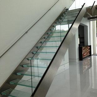 Foto di una scala a rampa dritta minimal di medie dimensioni con pedata in vetro e nessuna alzata