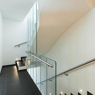 Esempio di una scala a rampa dritta contemporanea con parapetto in vetro e pedata piastrellata