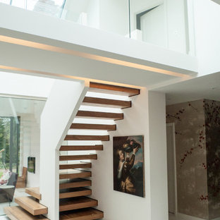 Inspiration for a large contemporary wood staircase in London with open risers.