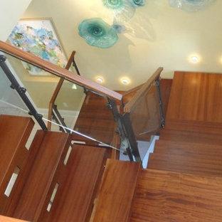 Foto de escalera en L, clásica, grande, con escalones de hormigón, contrahuellas de hormigón y barandilla de vidrio