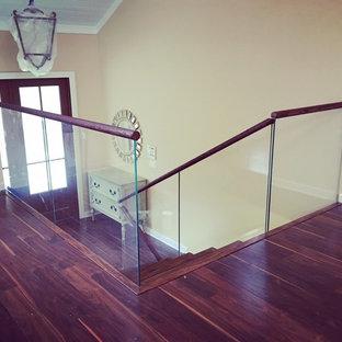 Ejemplo de escalera recta, moderna, de tamaño medio, con escalones de madera, contrahuellas de madera y barandilla de vidrio