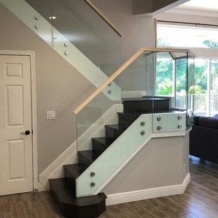 Modelo de escalera en L, moderna, de tamaño medio, con escalones de madera, contrahuellas de madera y barandilla de vidrio