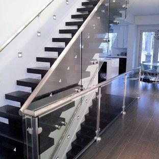 Diseño de escalera suspendida, minimalista, grande, con escalones de madera pintada y barandilla de vidrio