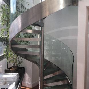 Imagen de escalera de caracol y madera, actual, de tamaño medio, sin contrahuella, con escalones de vidrio, barandilla de vidrio y madera