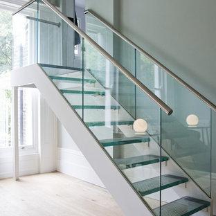 他の地域の中くらいのガラスのモダンスタイルのおしゃれな階段 (ガラスの手すり) の写真