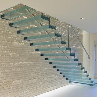 Immagine di una scala sospesa minimalista di medie dimensioni con pedata in vetro, nessuna alzata e parapetto in vetro