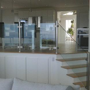 Imagen de escalera recta, actual, de tamaño medio, con escalones de madera y contrahuellas de vidrio