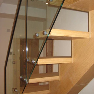 Inspiration for a modern wooden straight staircase remodel in Other with glass risers