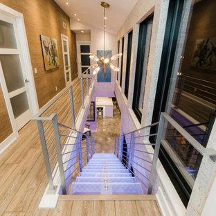 Foto de escalera suspendida y papel pintado, minimalista, grande, sin contrahuella, con escalones de vidrio, barandilla de metal y papel pintado