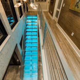 Foto de escalera suspendida y papel pintado, moderna, grande, sin contrahuella, con escalones de vidrio, barandilla de metal y papel pintado