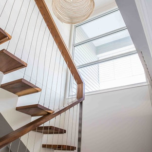 Imagen de escalera en U, costera, de tamaño medio, sin contrahuella, con escalones de madera y barandilla de varios materiales