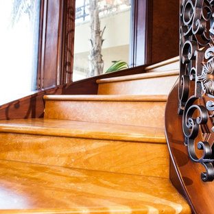 Esempio di una grande scala curva tradizionale con pedata in pietra calcarea, alzata in pietra calcarea e parapetto in metallo