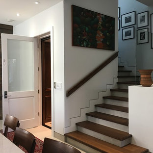 """Esempio di una scala a """"L"""" minimal di medie dimensioni con pedata in legno, alzata in cemento e parapetto in legno"""