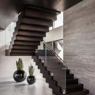Стильный дизайн: большая п-образная лестница в современном стиле с деревянными ступенями, деревянными подступенками и стеклянными перилами - последний тренд