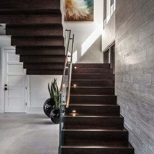 Пример оригинального дизайна: большая лестница на больцах в современном стиле с деревянными ступенями, стеклянными подступенками и металлическими перилами