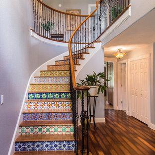 タンパの広い木の地中海スタイルのおしゃれなサーキュラー階段 (タイルの蹴込み板) の写真