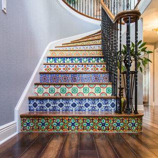 Diseño de escalera curva, ecléctica, grande, con escalones de madera y contrahuellas con baldosas y/o azulejos