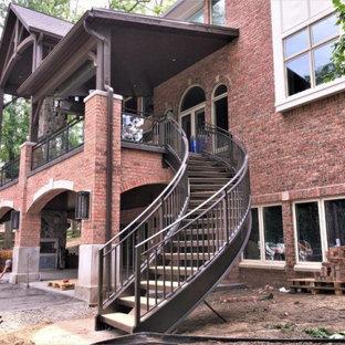 Modelo de escalera curva y ladrillo, clásica, grande, sin contrahuella, con escalones de madera, barandilla de metal y ladrillo