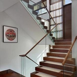 """Idee per una grande scala a """"U"""" minimal con pedata in legno, alzata in legno e parapetto in vetro"""