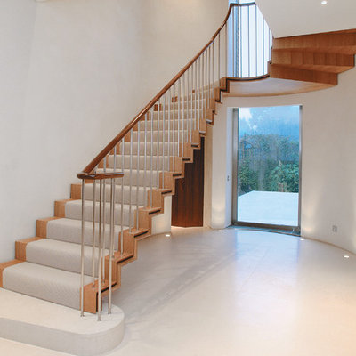 Trendy wooden u-shaped staircase photo in London with wooden risers