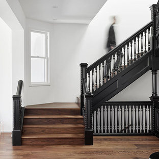 Photo of a large classic wood u-shaped staircase in San Francisco with wood risers.