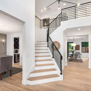 Идея дизайна: большая изогнутая лестница в современном стиле с деревянными ступенями, крашенными деревянными подступенками и металлическими перилами
