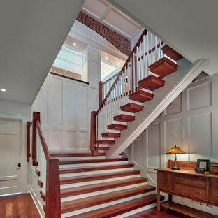 Diseño de escalera en U, de estilo americano, con escalones de madera, contrahuellas de madera pintada y barandilla de madera