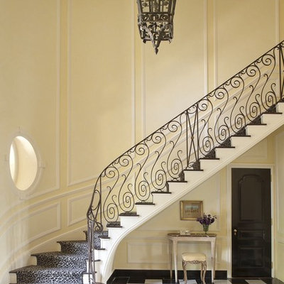 Elegant wooden curved staircase photo in New York with painted risers