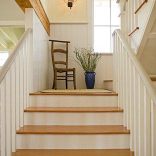 Стильный дизайн: п-образная лестница в морском стиле с деревянными ступенями и крашенными деревянными подступенками - последний тренд