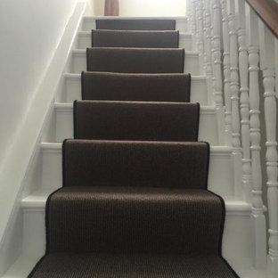 ロンドンのカーペット敷きのコンテンポラリースタイルのおしゃれな折り返し階段 (カーペット張りの蹴込み板、木材の手すり) の写真