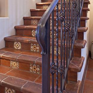 フェニックスの中サイズのタイルのサンタフェスタイルのおしゃれなかね折れ階段 (タイルの蹴込み板) の写真