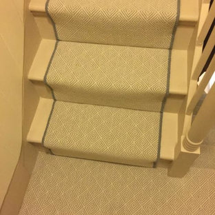 Example of a trendy carpeted u-shaped wood railing staircase design in London with carpeted risers