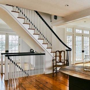 ニューヨークの中くらいの木のトラディショナルスタイルのおしゃれなかね折れ階段 (フローリングの蹴込み板、木材の手すり、パネル壁) の写真